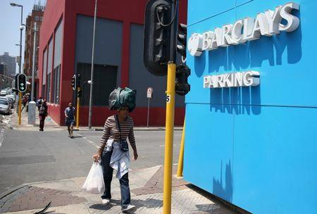 A women carries her belongings on her head as she walks past a Barclays logo in Johannesburg