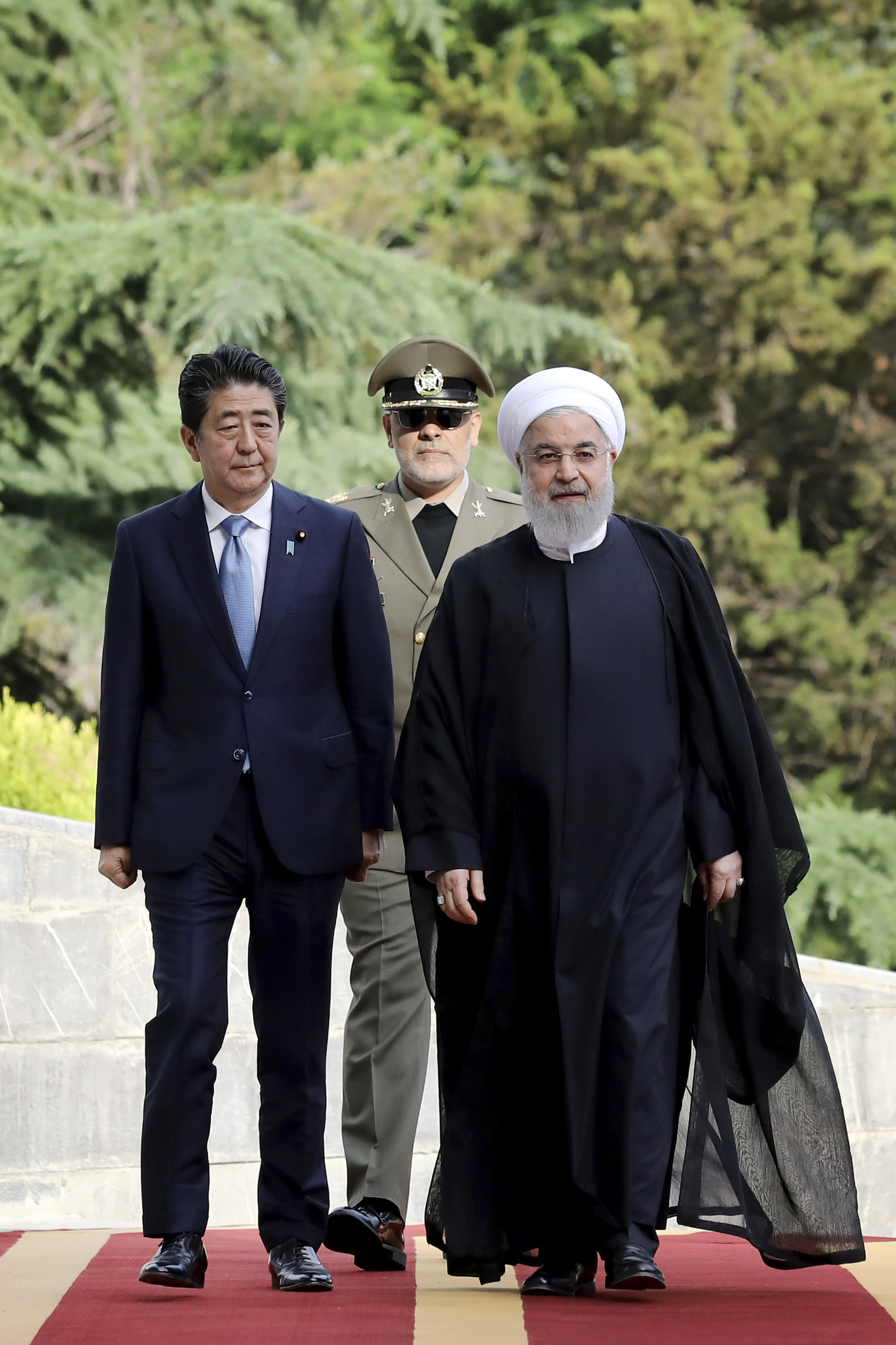 Japanese Prime Minister Shinzo Abe, left, is welcomed by Iranian President Hassan Rouhani, right, during an official arrival ceremony at the Saadabad Palace in Tehran, Iran, Wednesday, June 12, 2019. The Japanese leader is in Tehran on an mission to calm tensions between the U.S. and Iran. (AP Photo/Ebrahim Noroozi)