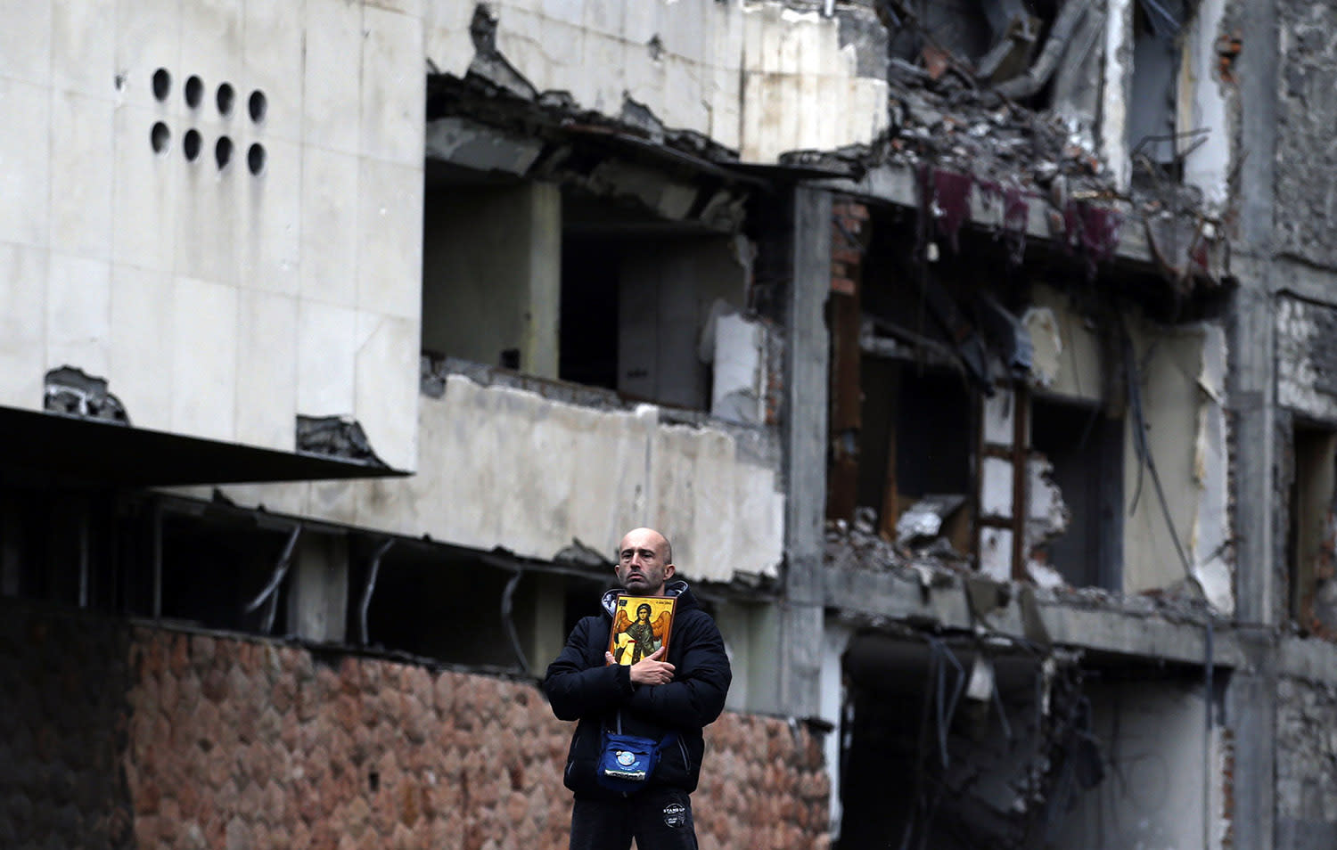 <p>A man holds an icon and stands in front of the destroyed former Yugoslav army headquarters, during a protest in Belgrade, Serbia, April 8, 2017. Thousands of people are blowing whistles and banging pots outside the Serbian government headquarters to protest the election of powerful Prime Minister Aleksandar Vucic as the country's new president. (Photo: Darko Vojinovic/AP) </p>
