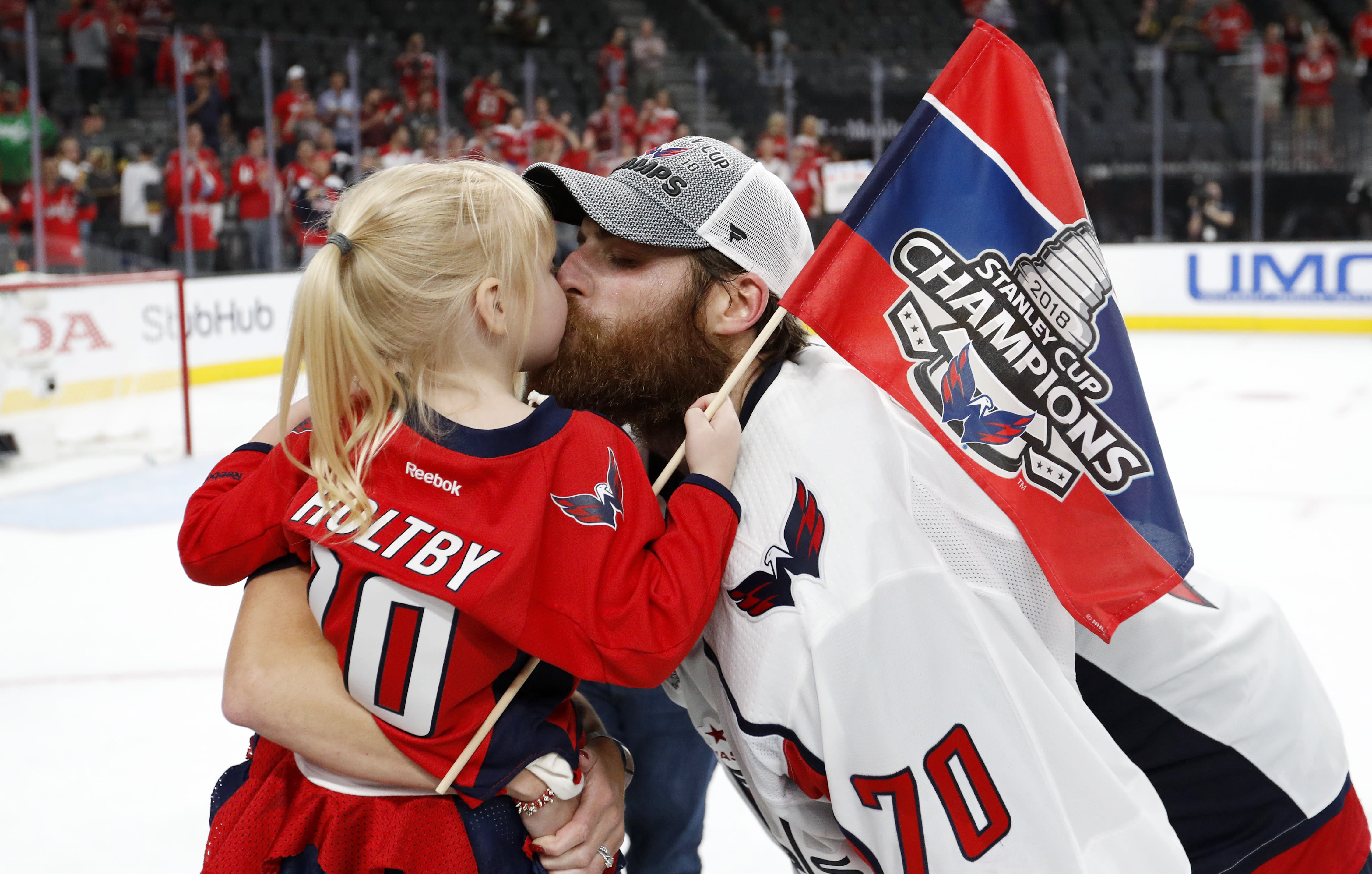 FILE - In this June 7, 2018, file photo, Washington Capitals goaltender Braden Holtby, right, kisses his daughter Belle after the Capitals defeated the Vegas Golden Knights 4-3 in Game 5 of the NHL hockey Stanley Cup Finals in Las Vegas. The past few weeks have seen several recent Stanley Cup winners get rid of members of their championship core. The Chicago Blackhawks moved on from Corey Crawford, the Washington Capitals did the same with Braden Holtby, the Pittsburgh Penguins traded fellow goalie Matt Murray and forward Patric Hornqvist and the St. Louis Blues signing Torey Krug means captain Alex Pietrangelo will sign elsewhere. (AP Photo/John Locher, File)