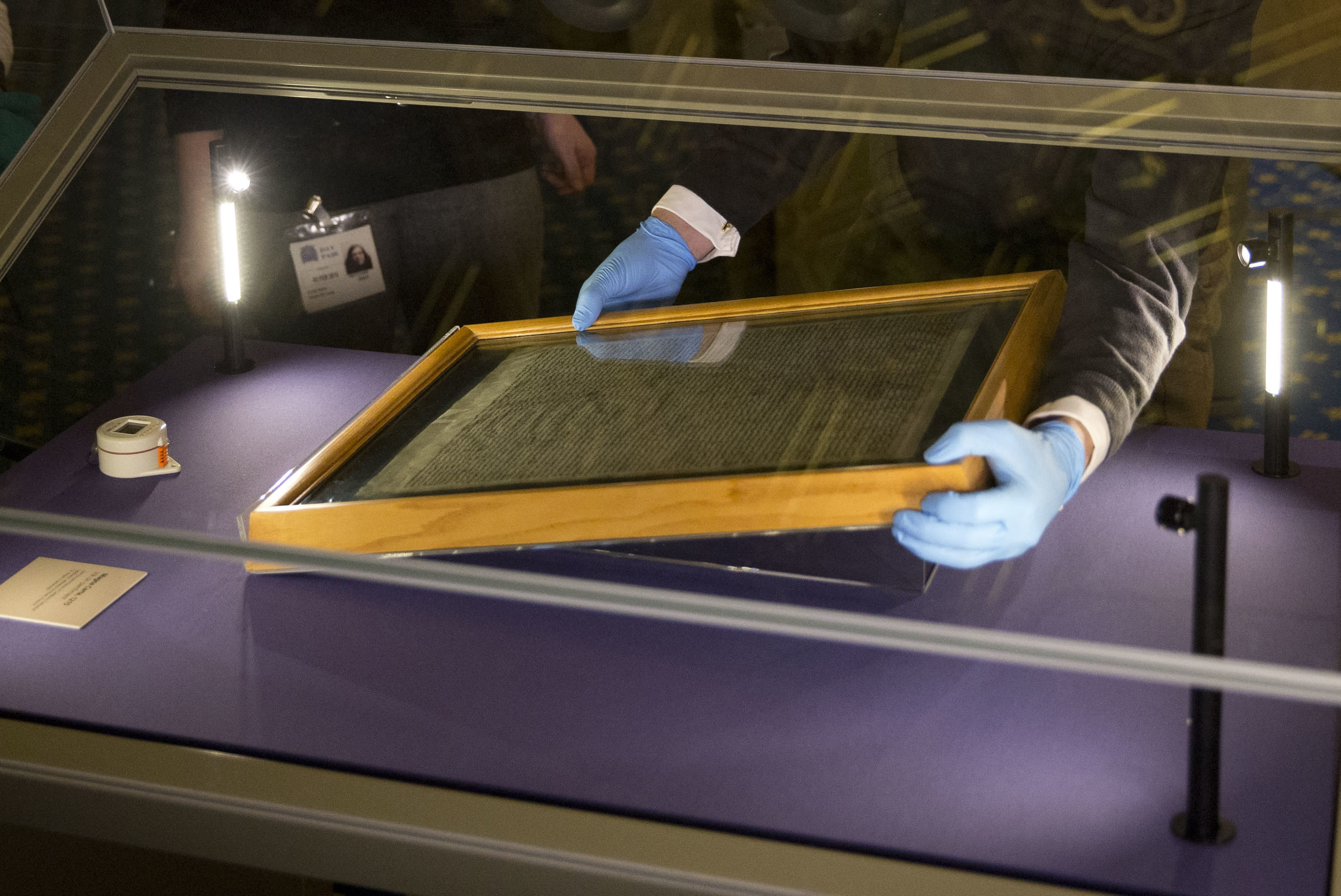 FILE - In this file photo dated Thursday, Feb. 5, 2015, The Salisbury Cathedral 1215 copy of the Magna Carta is installed in a glass display cabinet marking the 800th anniversary of the sealing of Magna Carta at Runnymede in 1215, in Salisbury, England. British police said Friday Oct. 26, 2018, that cathedral alarms sounded Thursday afternoon when a person tried to smash the glass display box surrounding the Magna Carta in Salisbury Cathedral, and a man has been arrested. (AP Photo/Matt Dunham, FILE)