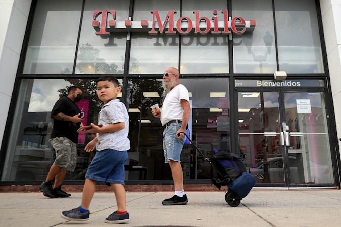 ARLINGTON, VA - AUGUST 18:  People walk past the front of a T-Mobile retail store on August 18, 2021 in Arlington, Virginia. T-Mobile announced Wednesday that a data breach exposed the personal information of 7.8 million current customers and 40 million people who had applied for credit. (Photo by Chip Somodevilla/Getty Images)