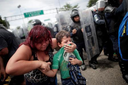 A Honduran migrant protects her child after migrants stormed the Guatemalan checkpoint to enter Mexico, in Ciudad Hidalgo
