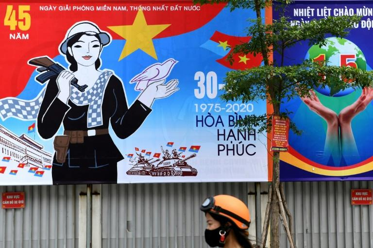 A woman walks next to a hoarding marking the 45th anniversary of the fall of Saigon, in Hanoi (AFP Photo/Nhac NGUYEN)