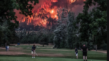 Stunning photo: Golfers play as Pacific Northwest wildfire rages behind them