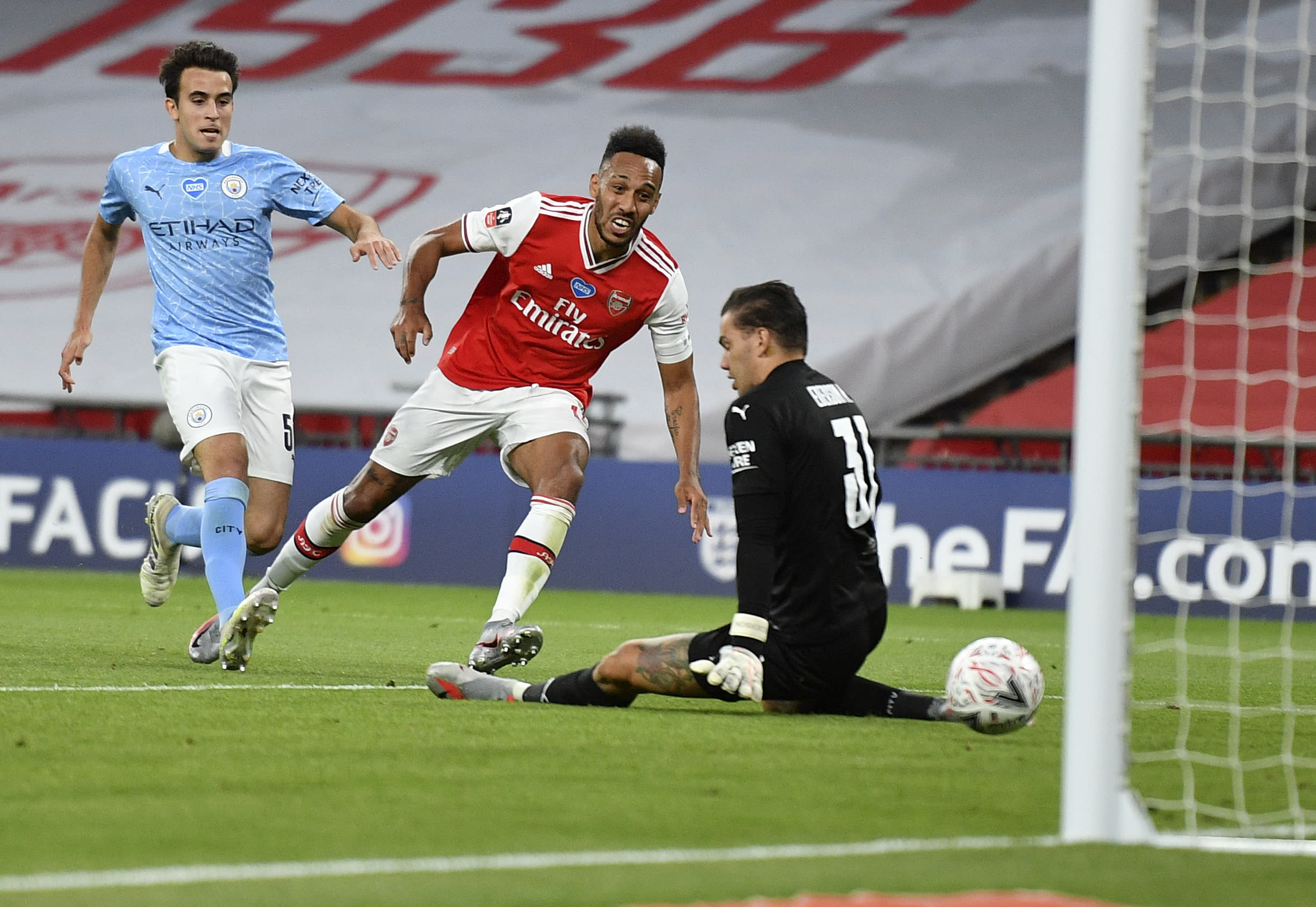 Arsenal's Pierre-Emerick Aubameyang, centre, scores his team's second goal during the FA Cup semifinal soccer match between Arsenal and Manchester City at Wembley in London, England, Saturday, July 18, 2020. (AP Photo/Justin Tallis,Pool)