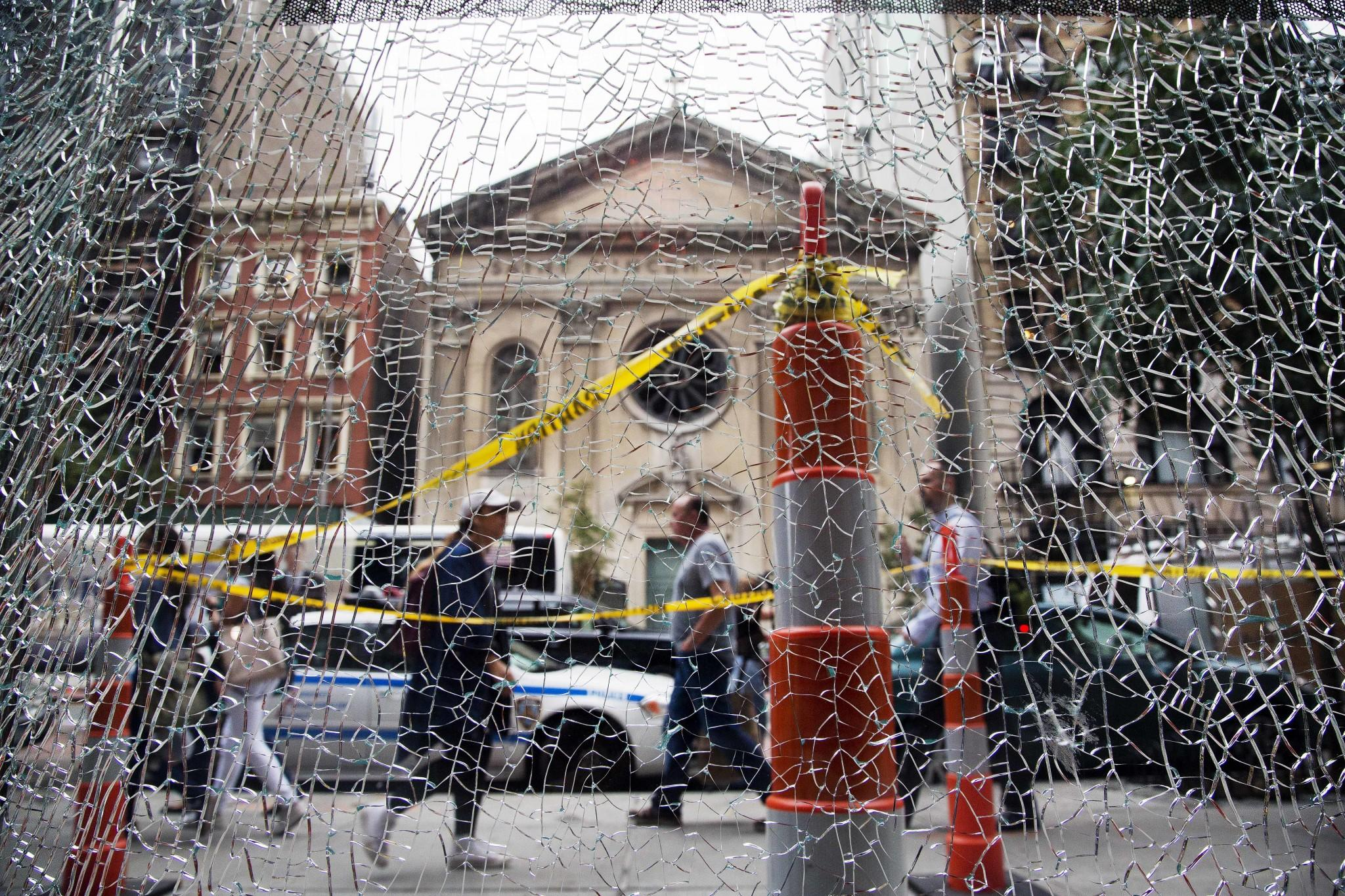 <p>New Yorkers pass a shattered storefront window on W. 23rd St. in Manhattan, Tuesday, Sept. 20, 2016, in New York. The window was hit by shrapnel from the bomb that exploded across the street Saturday evening. An Afghan immigrant wanted in the bombings was captured Monday after being wounded in a gun battle with police. (AP Photo/Mark Lennihan) </p>