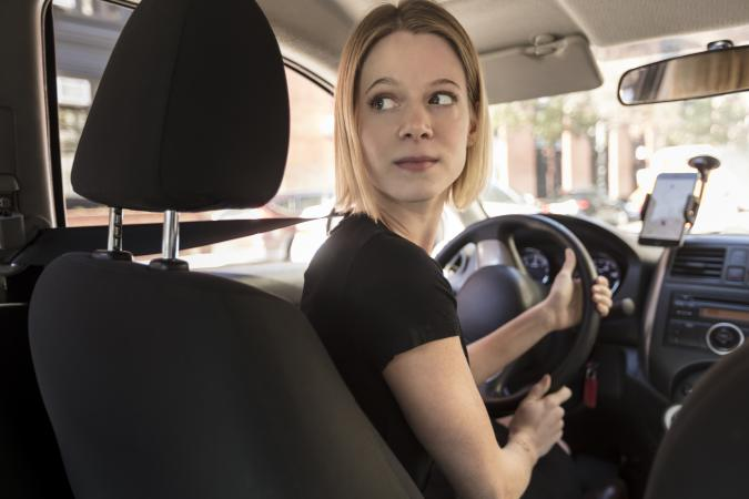 View from passenger in back seat of beautiful young blond woman driver, chauffeur driving a car with directions on her phone on a beautiful sunny day, Commute to work or to airport