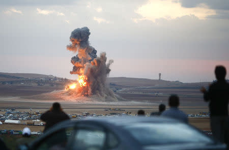 Smoke and flames rise over a hill near the Syrian town of Kobani after an airstrike