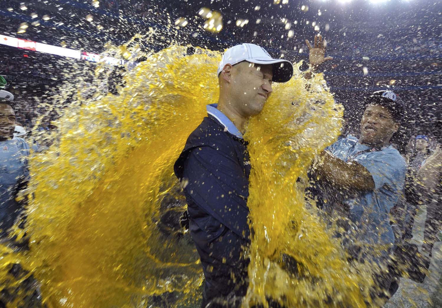 Toronto Argonauts head coach Scott Milanovich is doused by his players after the Argonauts defeated the Calgary Stampeders in the 100th CFL Grey Cup championship football game in Toronto, November 25, 2012. REUTERS/Mike Cassese