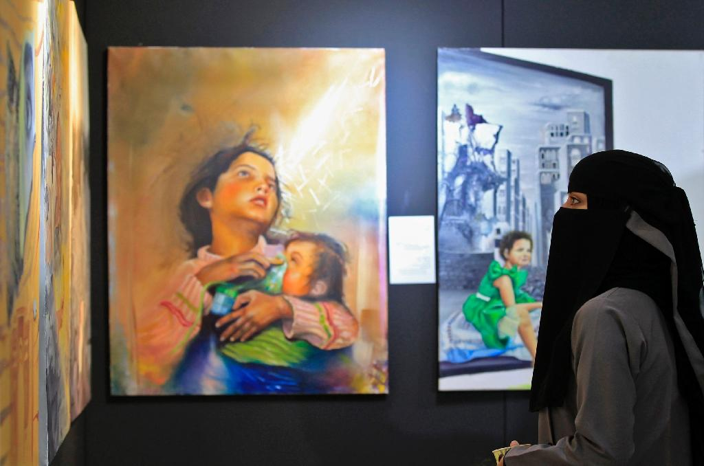 Yemenis visit an art exhibition aimed at showing the human cost of war in the rebel-held capital Sanaa on October 1, 2018 (AFP Photo/MOHAMMED HUWAIS)