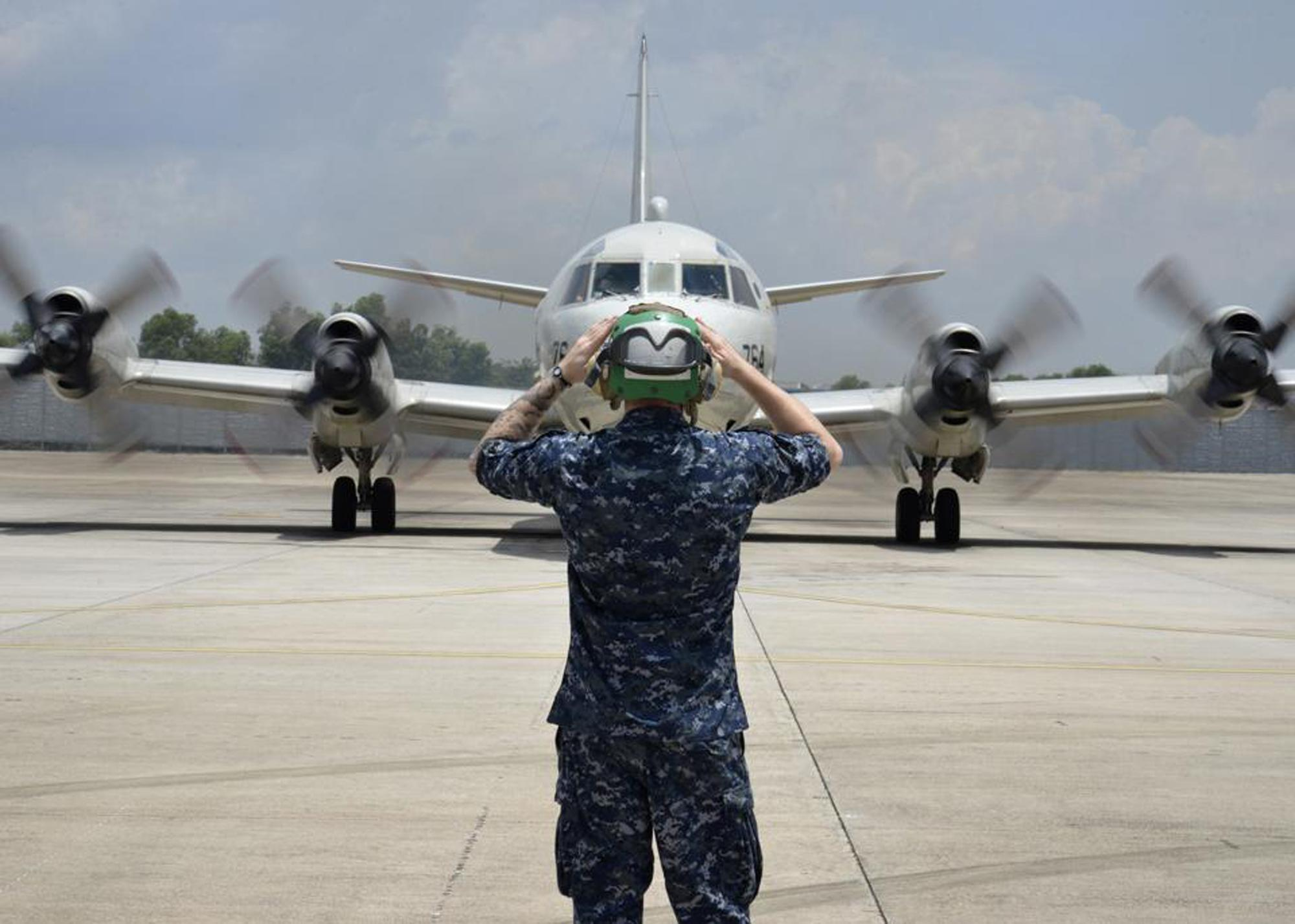 In this Monday, March 17, 2014 photo released by U.S. Navy, a sailor assigned to Patrol Squadron (VP) 46 prepares to launch a P-3C Orion before its mission to assist in search and rescue operations for Malaysia Airlines Flight 370 in Kuala Lumpur, Malaysia. New radar data from Thailand gave Malaysian investigators more potential clues Wednesday, March 19 for how to retrace the course of the missing Malaysian airliner, while a massive multinational search unfolded in an area the size of Australia. Cmdr. William Marks, a spokesman for the U.S. Navy's 7th Fleet, said finding the plane was like trying to locate a few people somewhere between New York and California. (AP Photo/U.S. Navy, Mass Communication Specialist 2nd Class Eric A. Pastor)