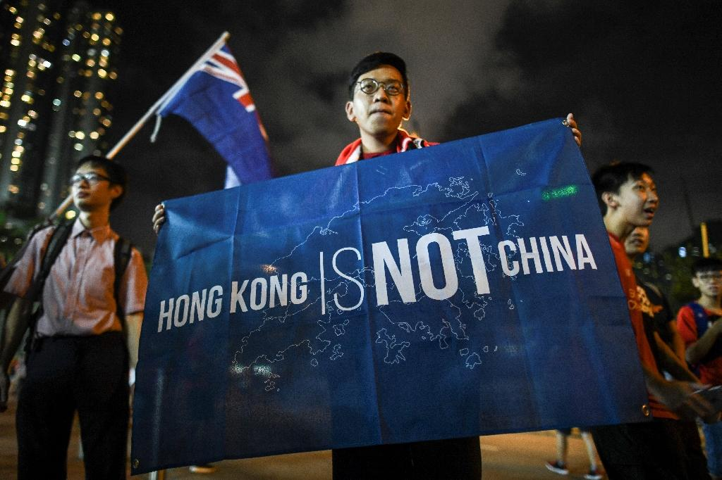 "In this picture taken on October 10, 2017, a flag that reads ""Hong Kong is not China"" is displayed by a local football fan in front of the old British colonial flag (back L) outside the stadium after a match between Hong Kong and Malaysia in Hong Kong (AFP Photo/ANTHONY WALLACE)"