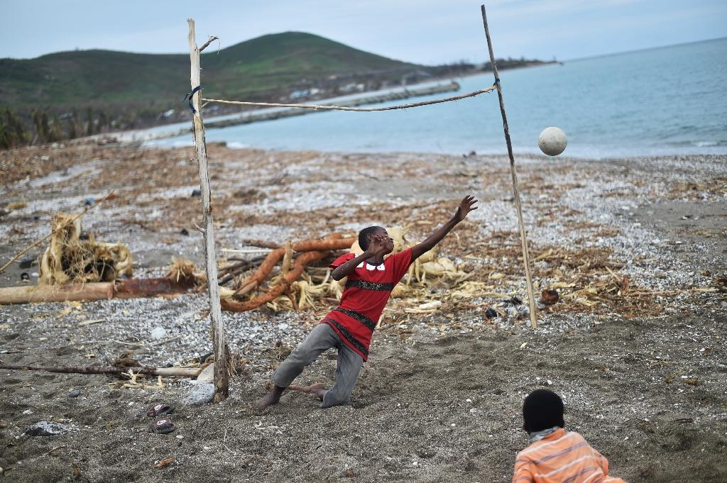 Children play fooball on a damaged beach on October 19, 2016 in the aftermath of Hurricane Matthew in the commune of Port-a-Piment, southwestern Haiti (AFP Photo/Hector Retamal)
