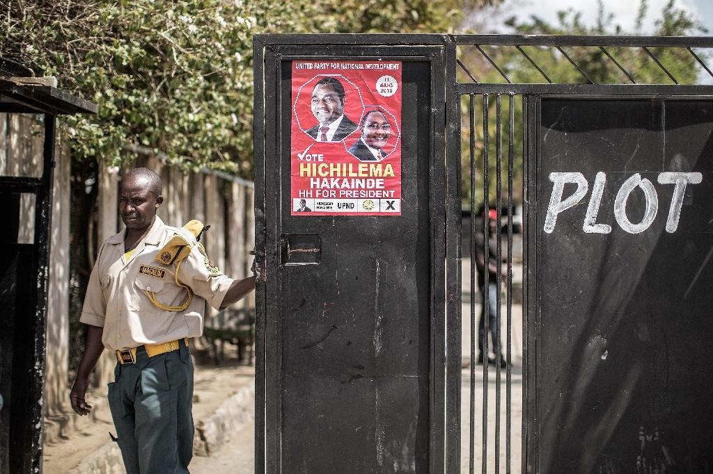 A security guard closes the gate at the headquarter of the United Party for National Development, opposition party of the presidential candidate Hakainde Hichilema on August 9, 2016 (AFP Photo/Gianluigi Guercia)
