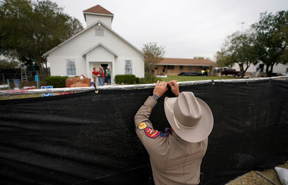 A Texas state trooper helps erect a fence around the site of the Sutherland Springs, Texas, shooting