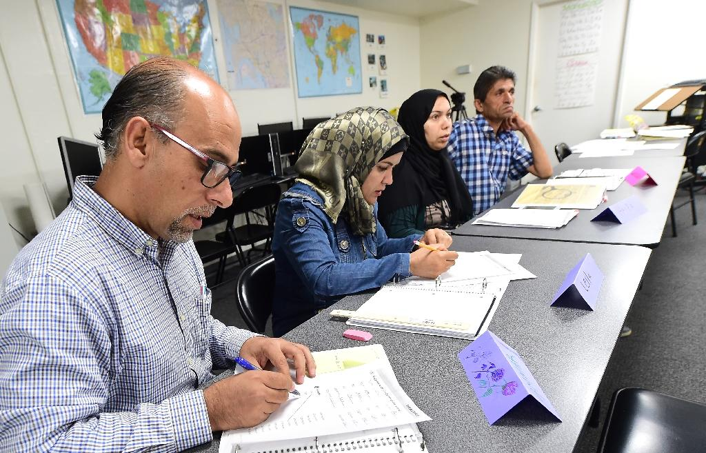 Syrian refugees take notes during their Vocational ESL class at the International Rescue Committee center in San Diego, on August 31, 2016 (AFP Photo/Frederic J. Brown)