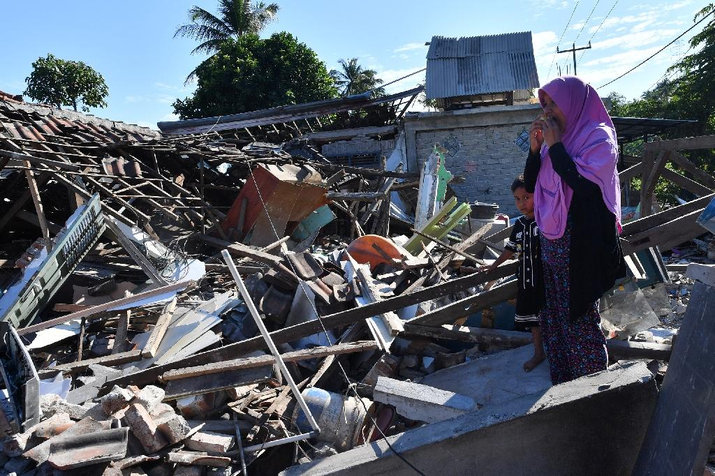 A woman and boy watch as men clear the wreckage of houses damaged by an earthquake in Menggala, North Lombok (AFP Photo/ADEK BERRY)