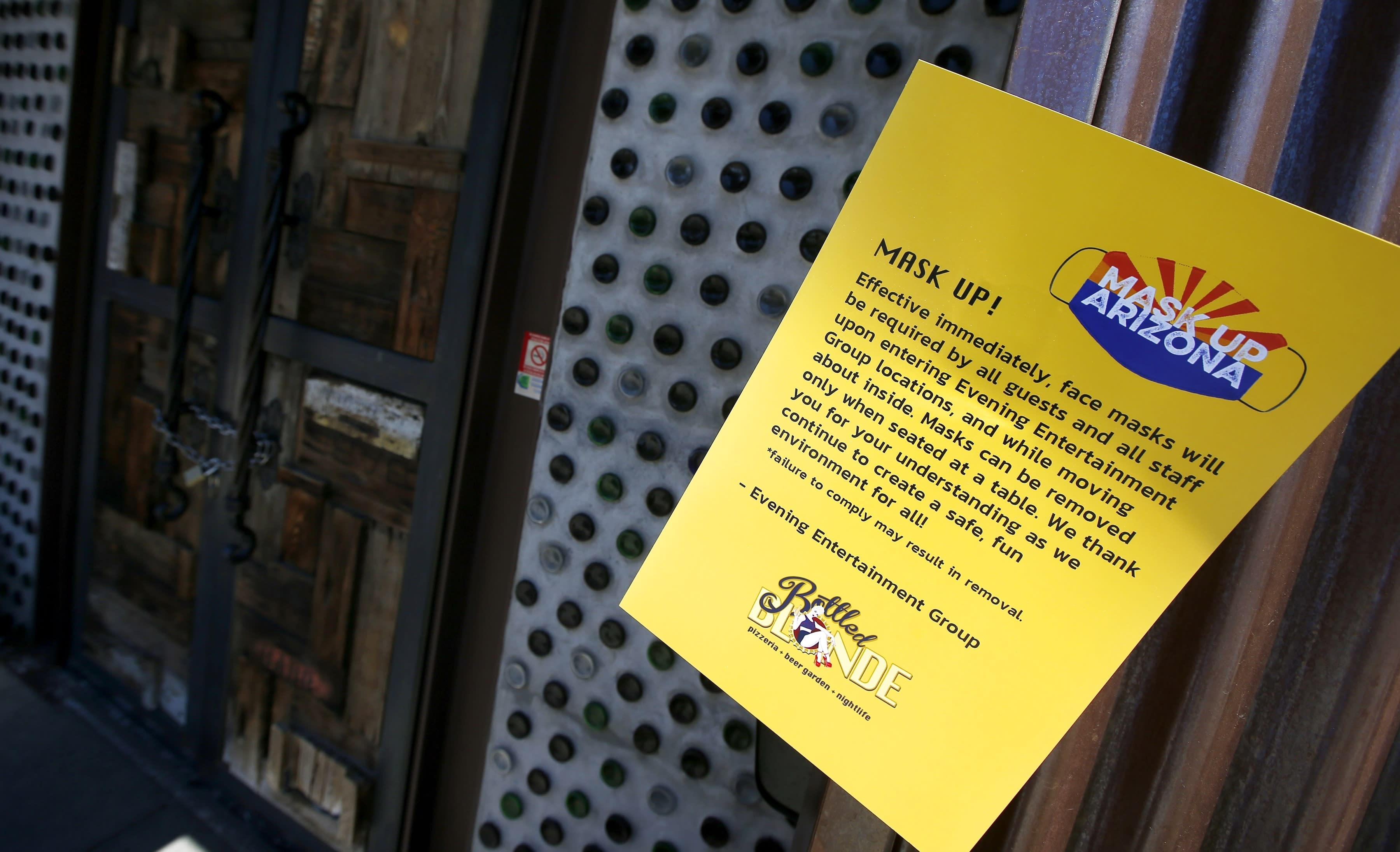 Bottled Blonde, one of the restaurant bars closed for the next 30 days due to the surge in coronavirus cases, has a posted rules sign but also has a padlocked front door Tuesday, June 30, 2020, in Scottsdale, Ariz. (AP Photo/Ross D. Franklin)