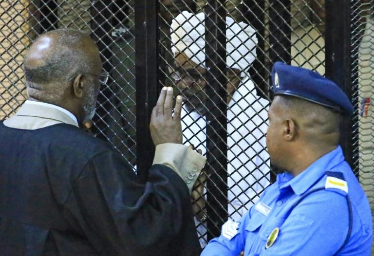 The deposed president sits in a defendant's cage during his corruption trial at a court in Khartoum in December last year (AFP Photo/-)