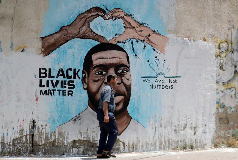 A Palestinian man walks past a mural depicting George Floyd, in Gaza City