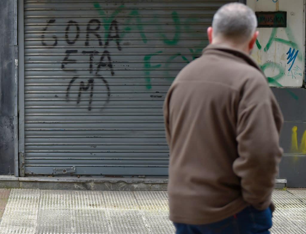 A man walks past a pro-ETA graffiti in the village of Hernani in Spain's Basque Country