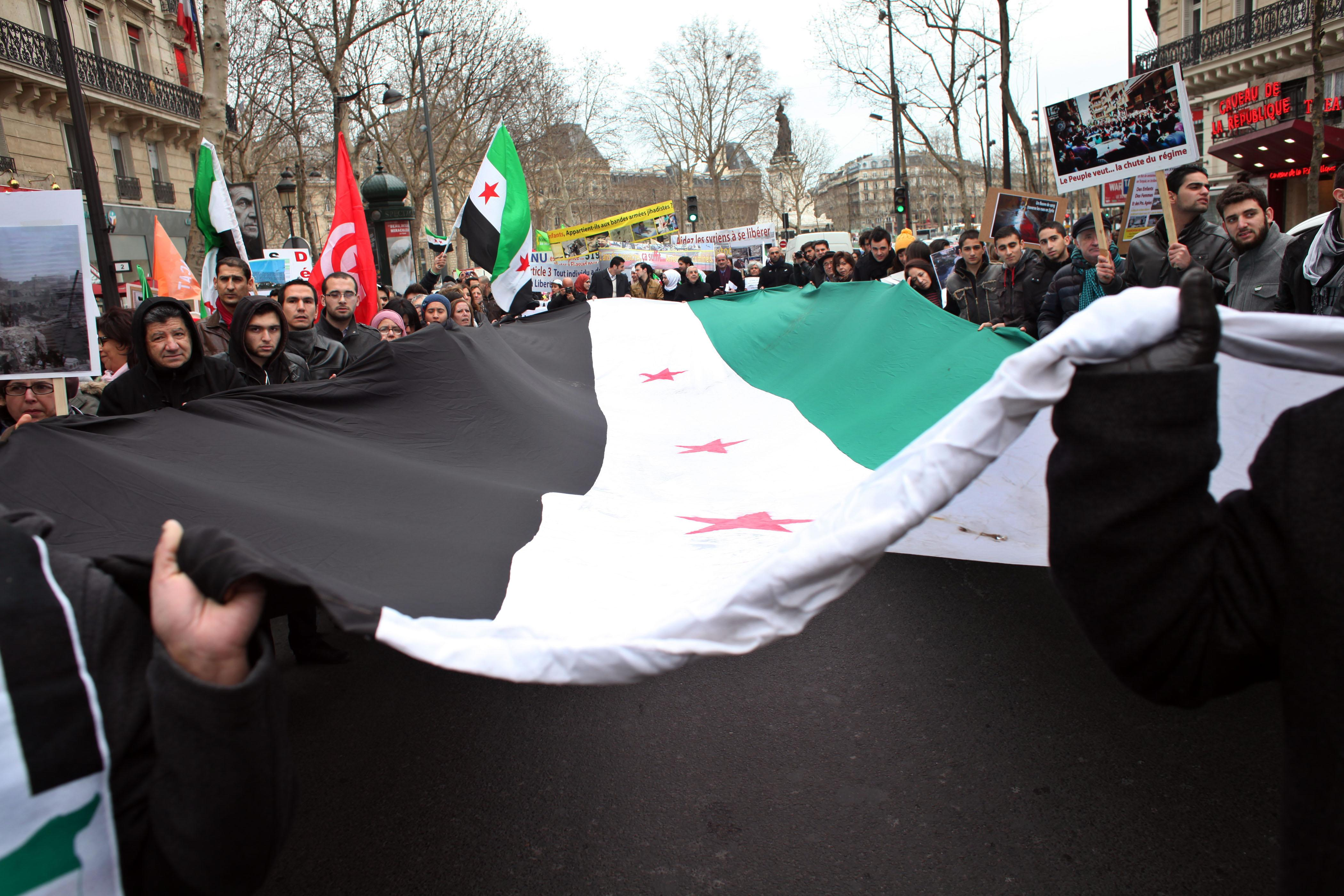 Demonstrators hold a giant Syrian flag during a march to mark the second anniversary of the revolt against government of Syrian President Bashar Assad, in Paris, Saturday, March 16, 2013. The French President Francois Hollande said Thursday his country and Britain are pushing the European Union to quickly lift its arms embargo on Syria so that they can send weapons to rebel fighters. (AP Photo/Thibault Camus)