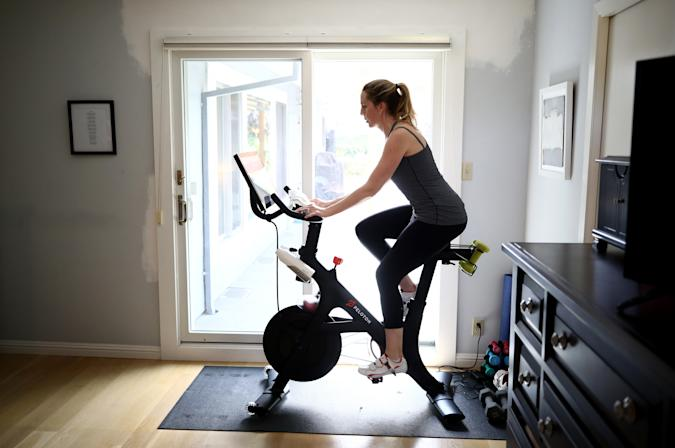 SAN ANSELMO, CALIFORNIA - APRIL 07:  Jen Van Santvoord rides her Peloton exercise bike at her home on April 07, 2020 in San Anselmo, California.  More people are turning to Peloton due shelter-in-place orders because of the coronavirus (COVID-19). The Peloton stock has continued to rise over recent weeks even as most of the stock market has plummeted. Peloton announced yesterday that they will temporarily pause all live classes until the end of April because an employee tested positive for COVID-19.  (Photo by Ezra Shaw/Getty Images)