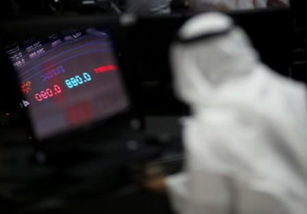 Reflection of stock market is seen on a screen as a trader monitors at Bahrain Bourse in Manama