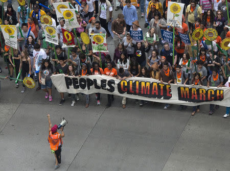 Activists hold a banner as they lead a march of tens of thousands down 6th Avenue during the People's Climate March through Midtown, New York