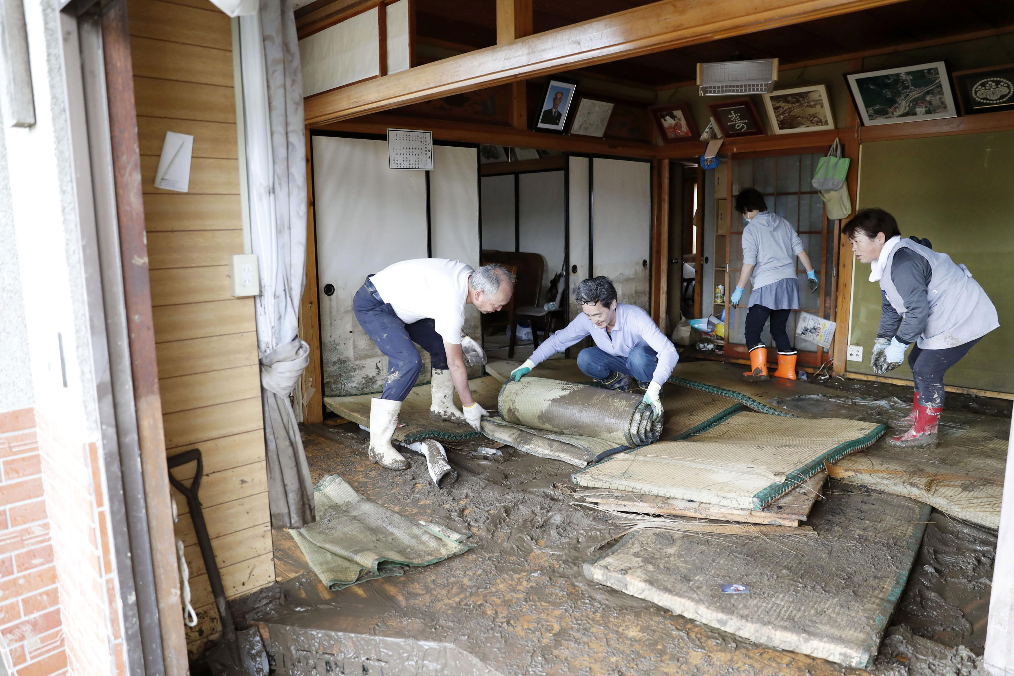 Residents clean a house damaged by Typhoon Hagibis, in Marumori town, Miyagi prefecture, Japan Monday, Oct. 14, 2019. Rescue crews in Japan dug through mudslides and searched near swollen rivers Monday as they looked for those missing from the typhoon that caused serious damage in central and northern Japan. (Kyodo News via AP)