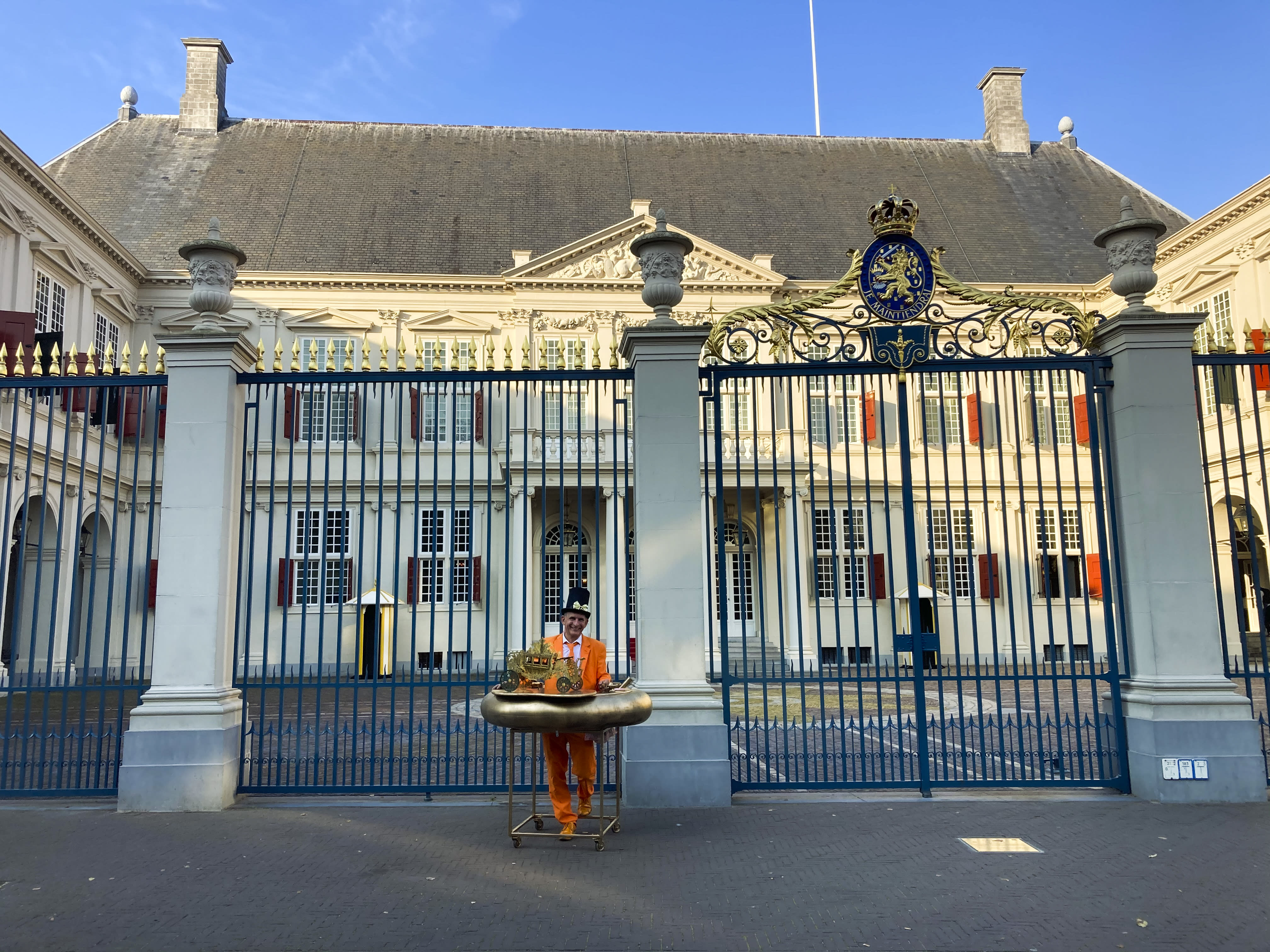 "Resplendent in orange suit, tie and shoes and a black hat with gold bow and protected by a homemade ""corona bumper"" decorated with a model carriage, Johan Vlemmix, center, stands in front of Royal Palace Noordeinde, in The Hague, Netherlands, Tuesday, Sept. 15, 2020. Vlemmix drove three hours to get to The Hague, as he has done every budget day for more than 20 years, to watch King Willem-Alexander and Queen Maxima appear on the palace balcony, rear. The balcony appearance of the king and queen has been cancelled due to COVID-19 related measures. ""It's surreal,"" he said. ""You see the red carpet has been rolled out, the king has arrived and there's nobody here. I've never experienced this. (AP Photo/Mike Corder)"