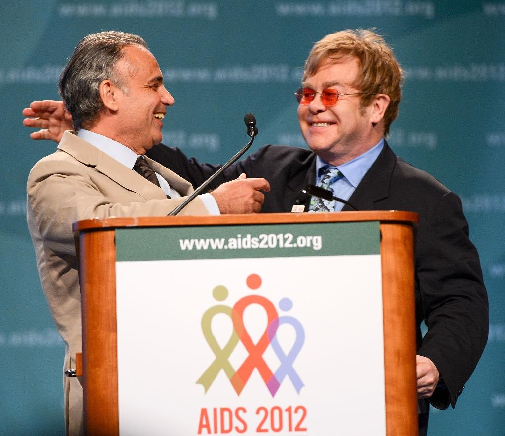 Former UNAIDS deputy director Luiz loures (L) welcomes Sir Elton John to the podium at the 19th International AIDS Conference at the Walter E. Washington Convention Center on July 23, 2012 in Washington, DC