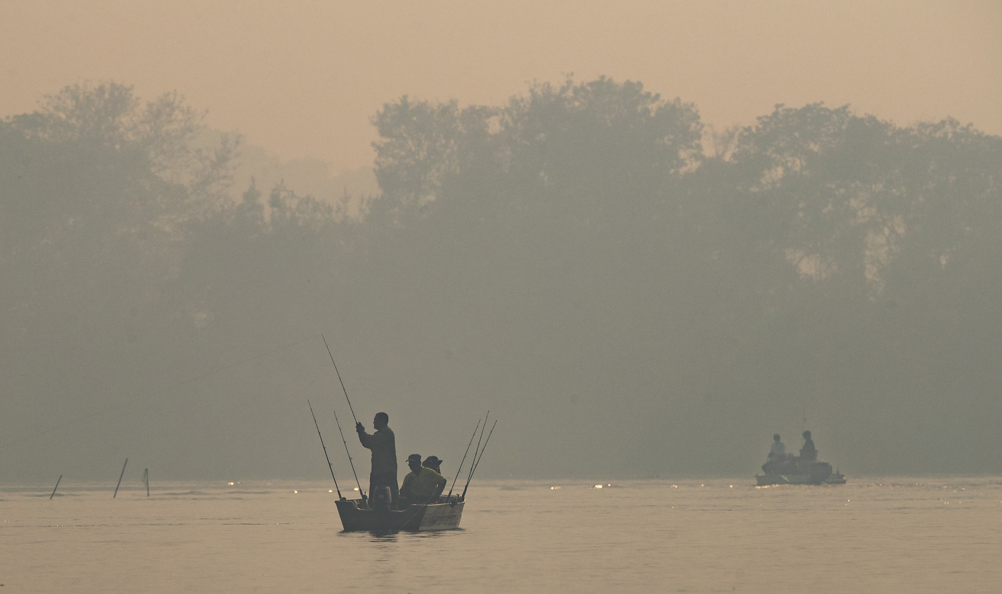 Men fish in the in the Cuiaba River in a dense smoke caused by fires, at the Encontro das Aguas state park in the Pantanal wetlands near Pocone, Mato Grosso state, Brazil, Sunday, Sept. 13, 2020. This year the Pantanal is exceptionally dry and burning at a record rate. The fires have been so intense that its smoke on Sept. 18 reached Sao Paulo, 900 miles away. (AP Photo/Andre Penner)