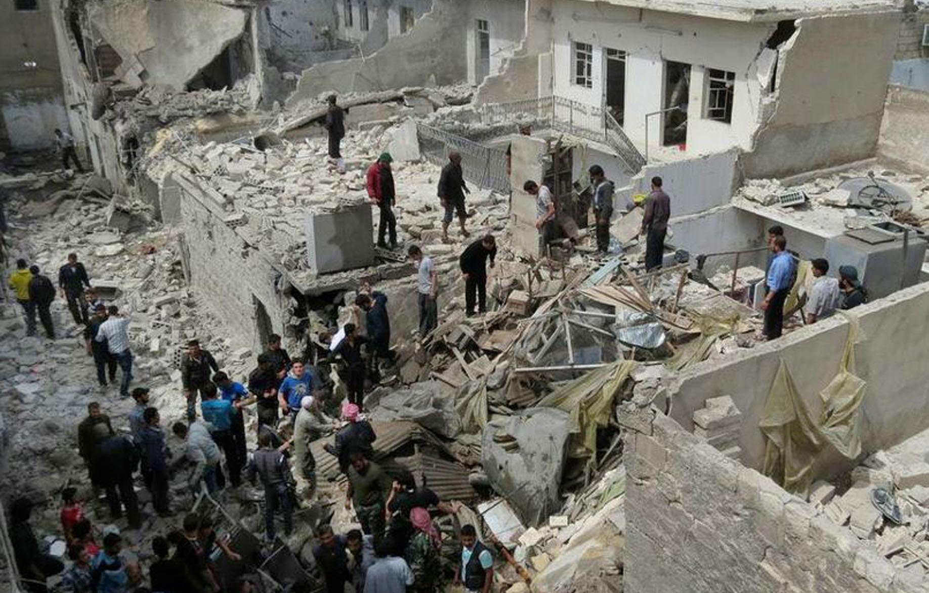 In citizen journalism image provided by Aleppo Media Center AMC which has been authenticated based on its contents and other AP reporting, Syrian citizens stand on rubble of destroyed houses that were damaged by Syrian forces airstrike, in Aleppo, Syria, Monday April 15, 2013. Syrian activists say government warplanes have carried out airstrikes around the country. The exiled leader of Syria's Muslim Brotherhood denied Monday widespread accusations by other pro-rebel political factions that the group is seeking to impose its will on other members of the opposition.(AP Photo/Aleppo Media Center, AMC)