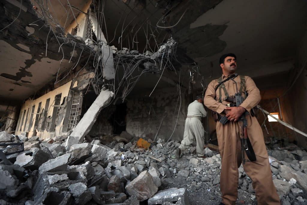Members of the Iranian Kurdistan Democratic Party (KDPI) check the damage after a rocket attack inside their headquarters in Koysinjaq, 100 kilometres east of Arbil, the capital of the autonomous Kurdish region of northern Iraq