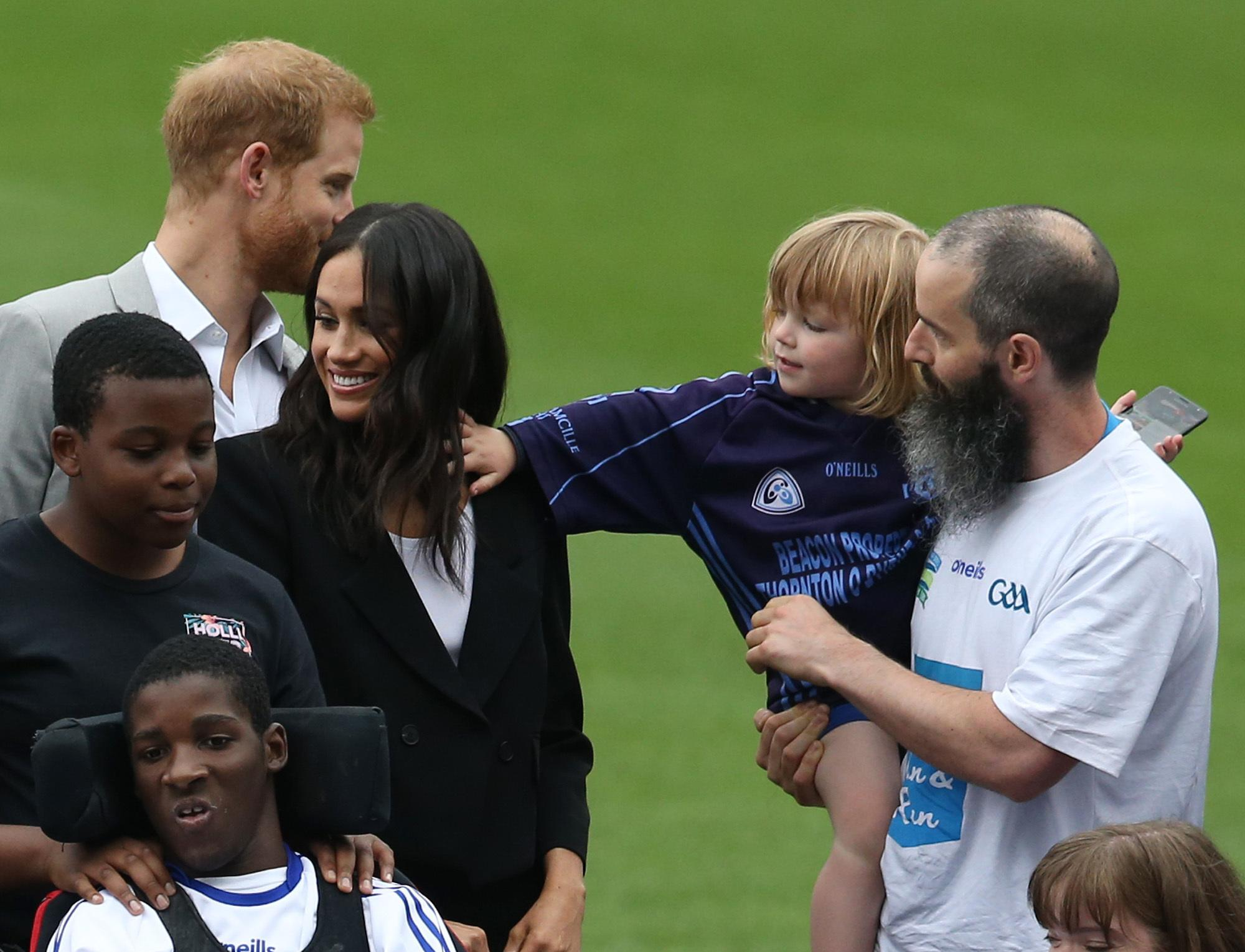 Walter Kieran, 3, reaches out to touch the Duchess of Sussex's hair during her visit with the Duke of Sussex to Croke Park in Dublin, Ireland.
