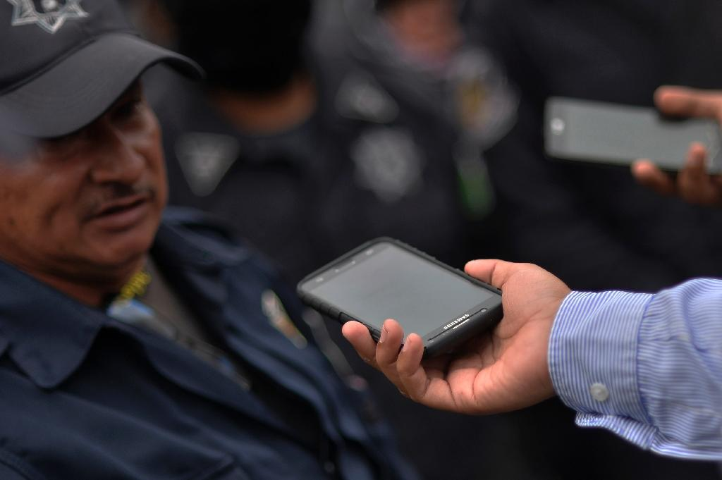 A Mexican journalist interviews a police officer during a protest rally in Chilpancingo, Guerrero state (AFP Photo/PEDRO PARDO)