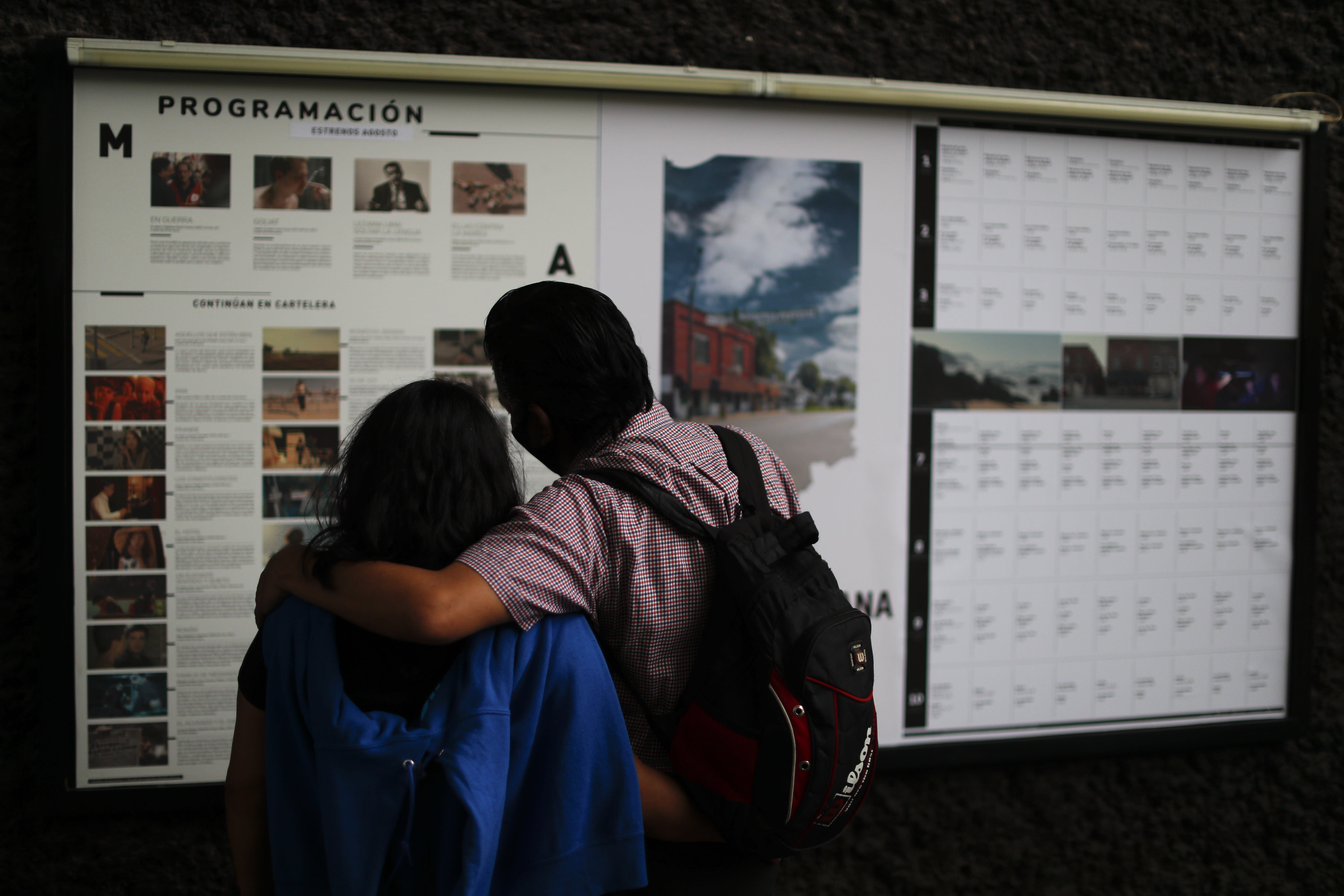 Filmgoers read listings for movies to be screened at the Cineteca Nacional, Mexico's film archive, in Mexico City, Wednesday, Aug. 12, 2020. After being closed for nearly five months amidst the ongoing coronavirus pandemic, movie theaters in the capital reopened Wednesday at 30% capacity. (AP Photo/Rebecca Blackwell)