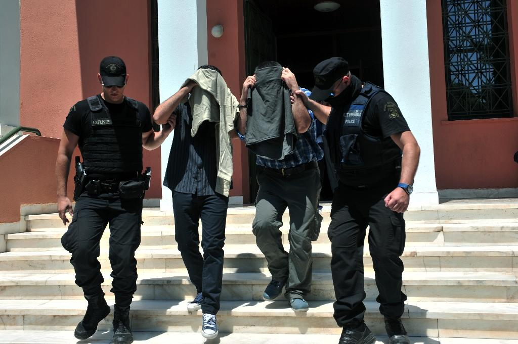 Turkish officers escorted by Greek police officers leave the courthouse of Alexandroupoli after appearing before a Greek prosecutor, on July 17, 2016 (AFP Photo/Sakis Mitrolidis)