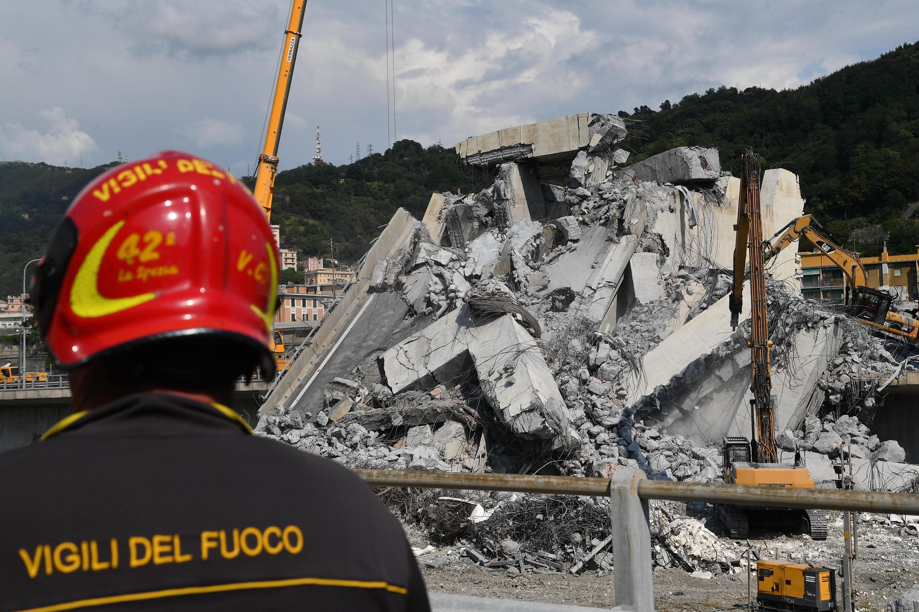 A firefighter look at caterpillars as they clear debris from the collapsed Morandi highway bridge, in Genoa, Italy, Friday, Aug. 17, 2018. Officials say 38 people are confirmed killed and 15 injured. Prosecutors say 10 to 20 people might be unaccounted-for and the death toll is expected to rise. (Luca Zennaro/ANSA via AP)