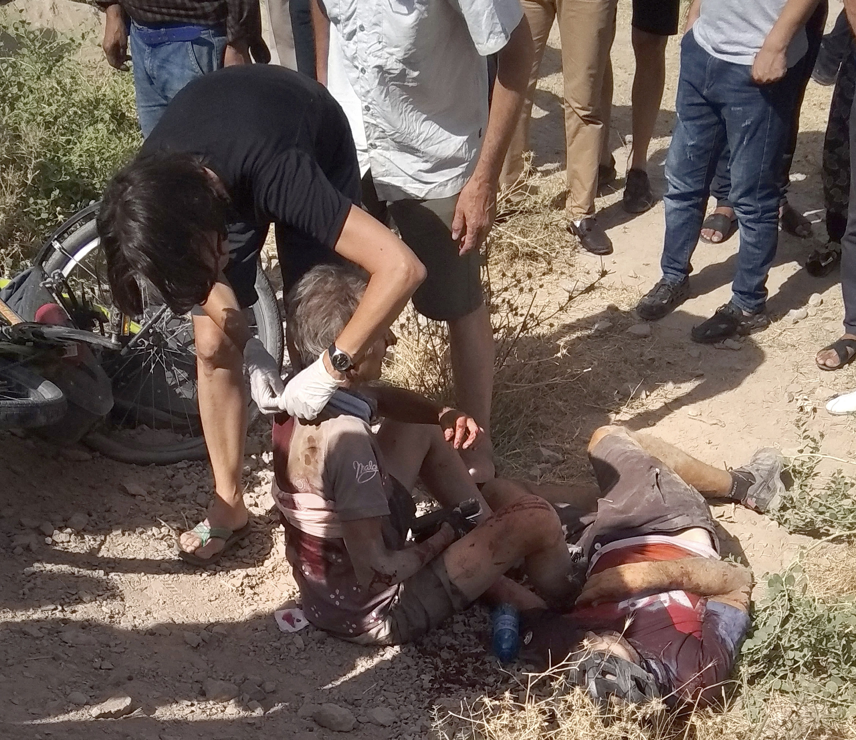 In this photo taken on Sunday, July 29, 2018, a woman helps a wounded cyclist, where the four tourists were killed when a car rammed into a group of foreigners on bicycles south of the capital of Dushanbe, Tajikistan. The Islamic State group on Tuesday claimed responsibility for a car-and-knife attack on Western tourists cycling in Tajikistan that killed two Americans and two Europeans. (AP Photo/Zuly Rahmatova)