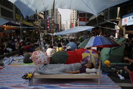 A pro-democracy protester sleeps on a bed as hundreds block Nathan Road, the main north-south route of Kowloon peninsula, at Hong Kong's Mongkok shopping district October 7, 2014. REUTERS/Bobby Yip