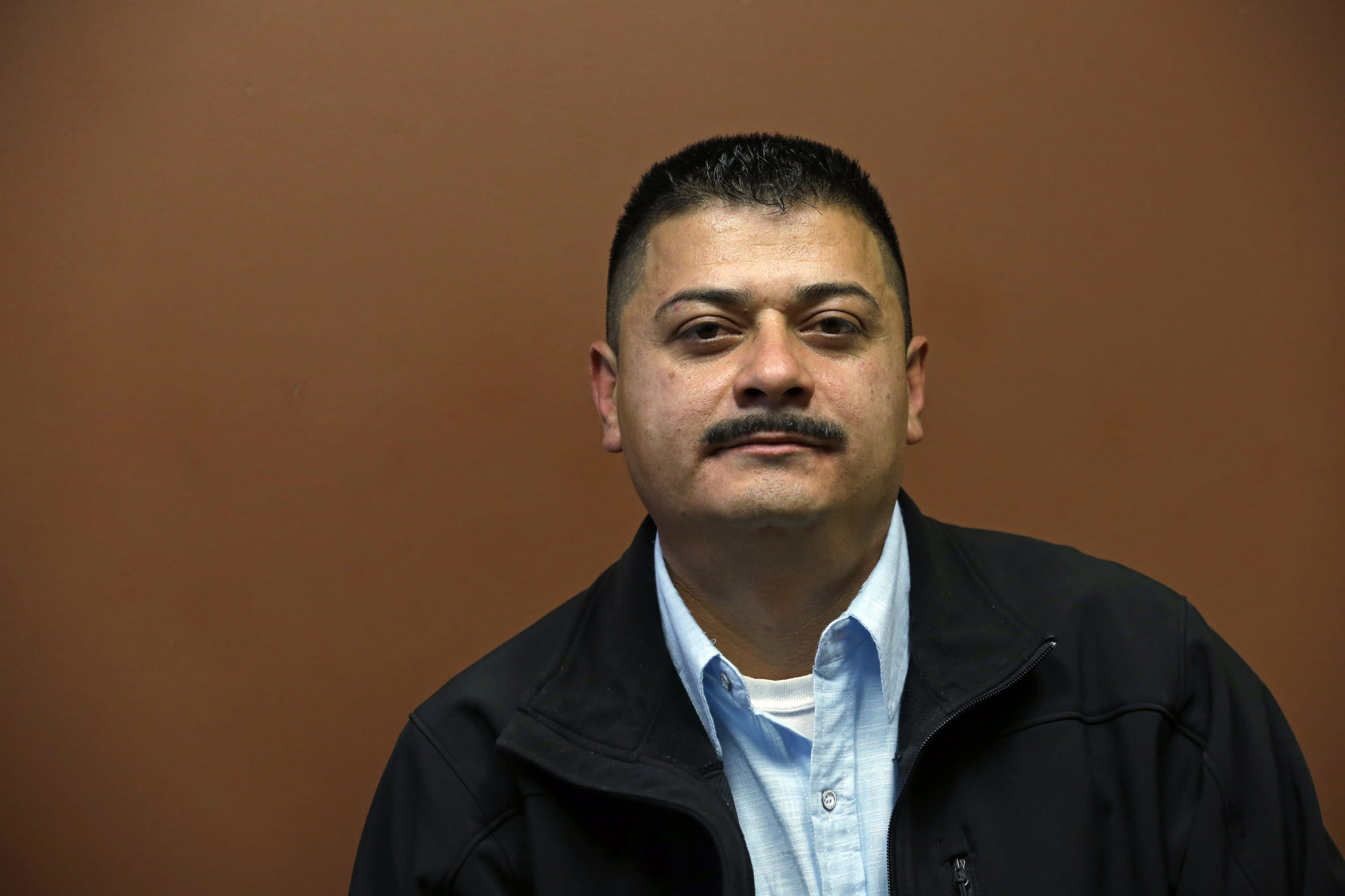 FILE - In this Oct. 17, 2014 file photo, Ignacio Lanuza sits for a portrait in Seattle. A federal judge on Tuesday, Oct. 29, 2019, criticized the Justice Department for seeking legal fees from Lanuza, a Mexican immigrant who was the victim of a forgery by a government lawyer. (AP Photo/Elaine Thompson, File)