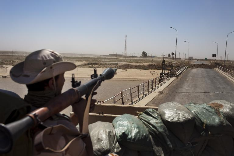 A Kurdish peshmerga fighter looks towards an Islamic State flag hoisted on the other side of a bridge on the road between Kirkuk and Tikrit, on September 11, 2014 (AFP Photo/Jm Lopez)