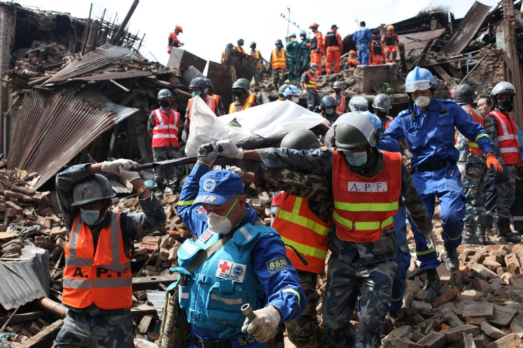 Picture taken on April 29, 2015 and released by the International Federation of Red Cross and Red Crescent Societies (IFRC) shows two bodies being excavated at Kolache-2, in Bhaktapur near Kathmandu (AFP Photo/Sailendra Kharel)
