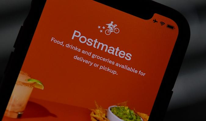 This illustration photo taken on June 30, 2020 shows the logo of delivery app Postmates on a smartphone screen in Los Angeles. - Uber is in talks to buy food delivery app Postmates in a multibillion dollar deal, US media reported. (Photo by Chris DELMAS / AFP) (Photo by CHRIS DELMAS/AFP via Getty Images)