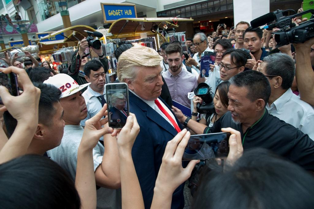 """Dubbed the """"real"""" Trump-Kim summit, the men waved at shoppers as they walked through the crowded Bugis Junction mall for a promotional event (AFP Photo/TOH TING WEI)"""