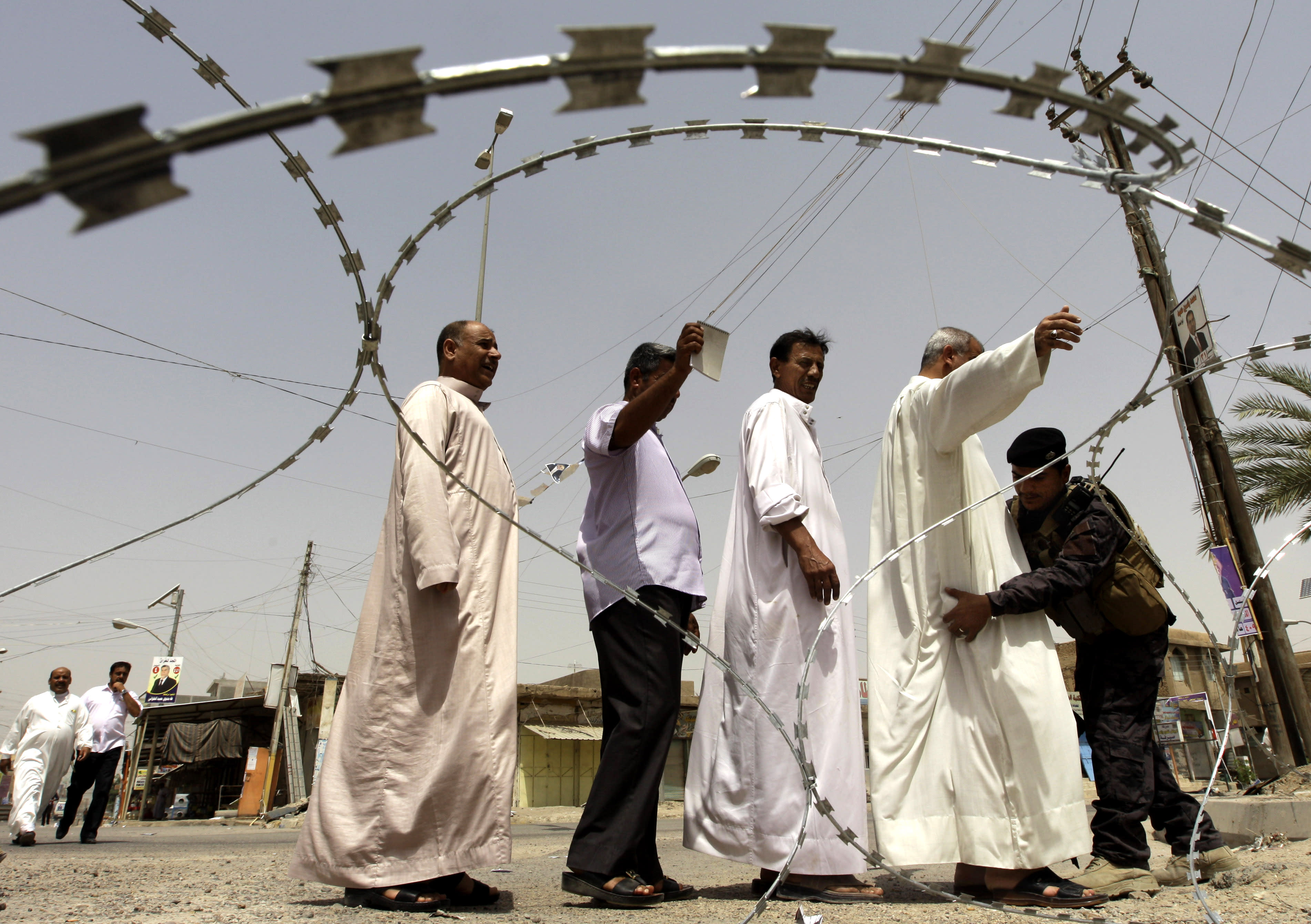 Iraqi citizens are searched before casting their votes during the country's provincial elections in Fallujah, Iraq, Thursday, June 20, 2013. Iraqis in two Sunni-dominated provinces voted Thursday in provincial elections marked by tight security measures that left streets in former insurgent strongholds largely deserted. (AP Photo/Khalid Mohammed)