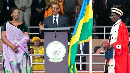 Rwanda's President-elect Paul Kagame (C) takes the oath of office as his wife Jeannette and Rwanda's Chief Justice Sam Rugege (R) look on during his swearing-in ceremony at Amahoro stadium in Kigali, Rwanda, August 18, 2017. REUTERS/Jean Bizimana